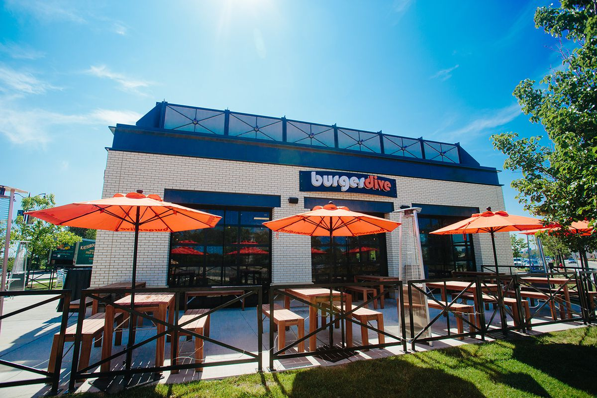 A low angle shows three orange umbrellas over tables outside the Burger Dive restaurant in Somerville