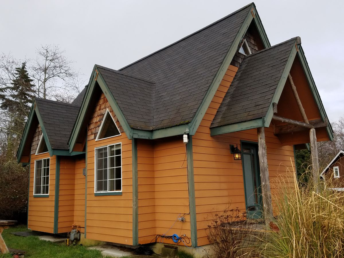 The exterior of an orange cottage with green trim and multiple roof peaks
