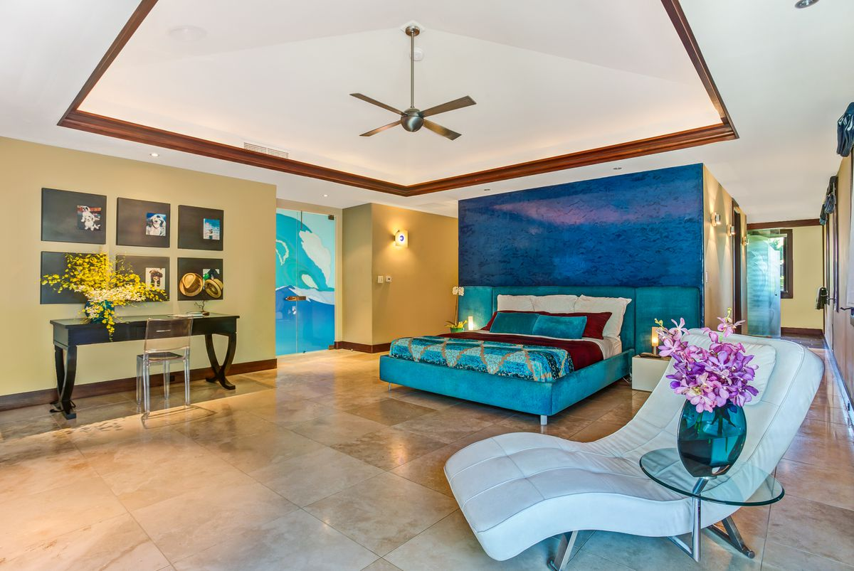 A teal and blue themed bedroom features an ensuite bath and raised ceilings.