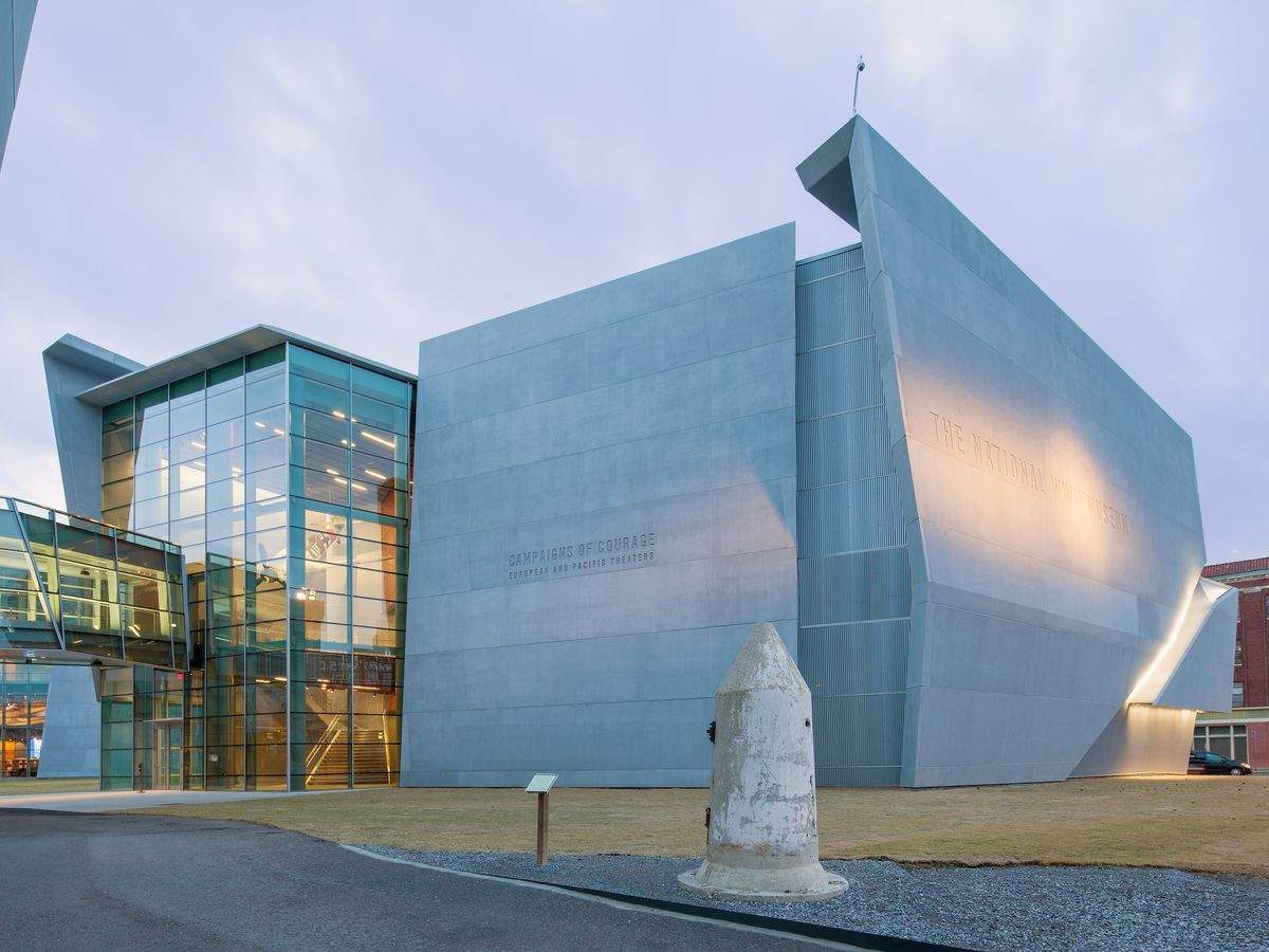 The exterior of the National WWII Museum. The facade has many windows and fabric covering over part of the structure.
