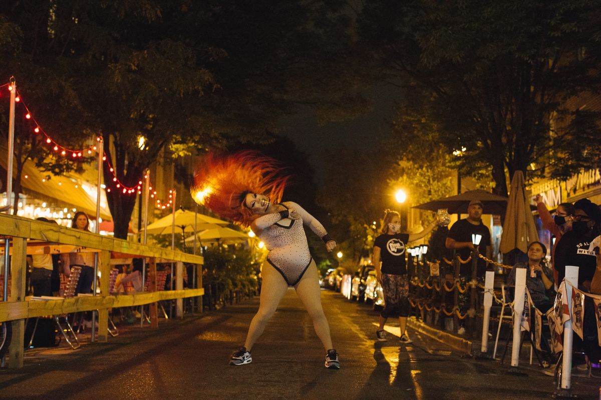 performer with long orange hair in the middle of the street with customers at tables on either side