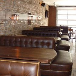oversized brown leather booths surround the bar area and comfortably seat six.