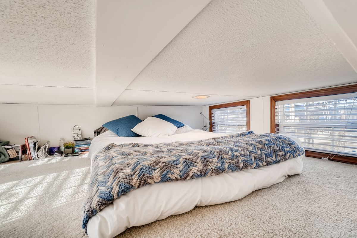 A lofted sleeping space features a bed on the floor, two windows, and short ceilings.