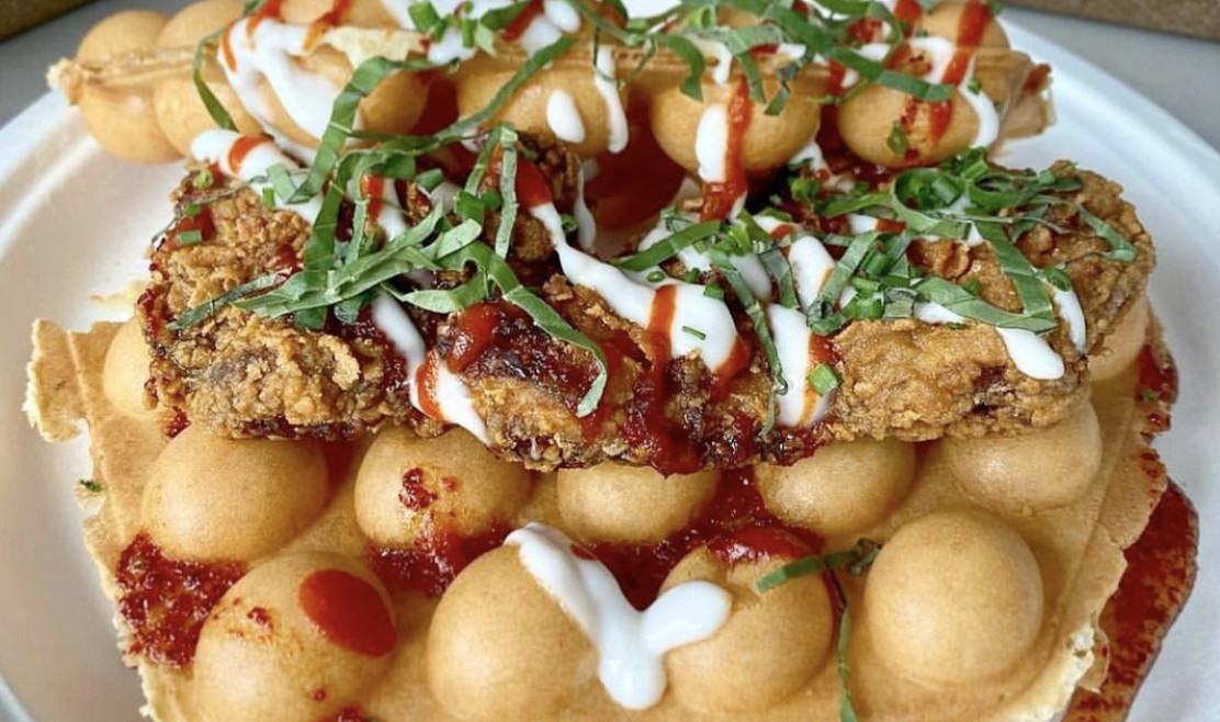 Fried chicken thigh on bubble waffles, with haupia syrup, hot honey, Sriracha, and basil