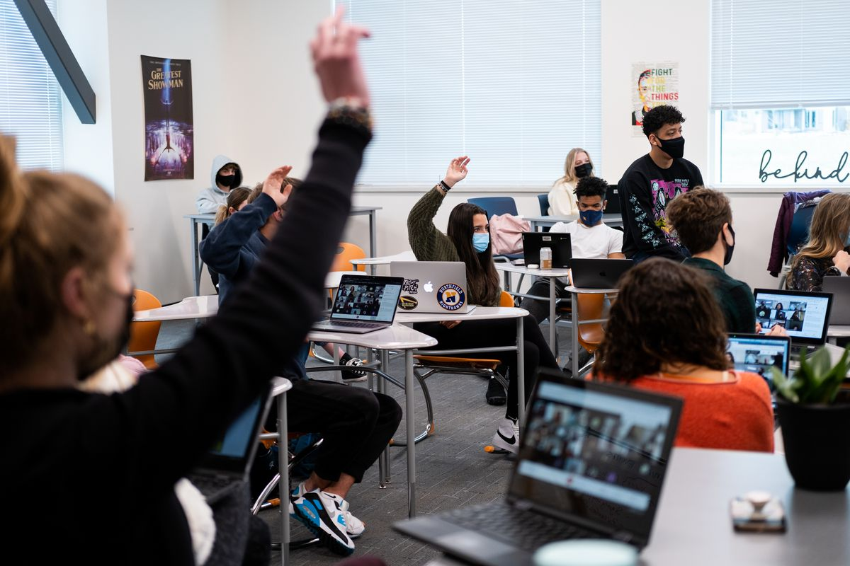 Students wearing masks sit in a Denver high school classroom. The students have open laptops on their desks. Several students are raising their hands.
