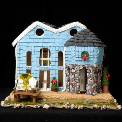 Gingerbread house designed with large windows and a wreath above the door.