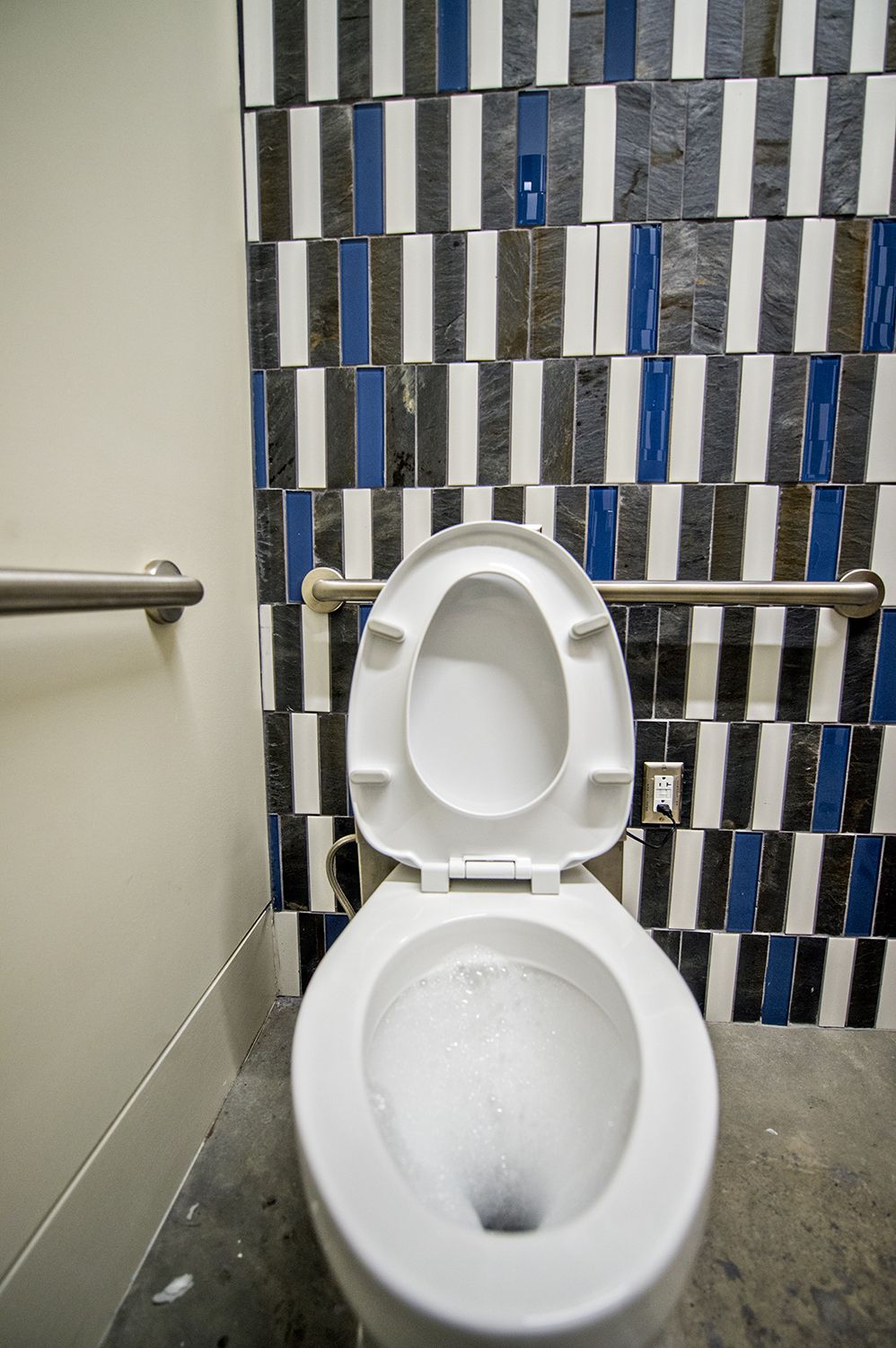 A toilet with a wall of slate tiling behind it and concrete floors.