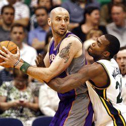 Sun's Marcin Gortat is guarded by Utah's Paul Millsap as the Utah Jazz and the Phoenix Suns play NBA basketball Wednesday, April 4, 2012, in Salt Lake City, Utah.