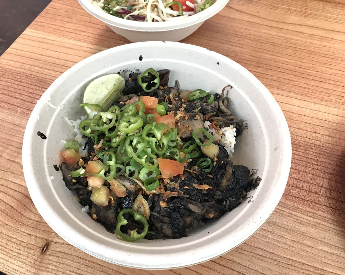A paper bowl filled with squid adobo on rice with a lime and sliced pepper sits on a wood table.