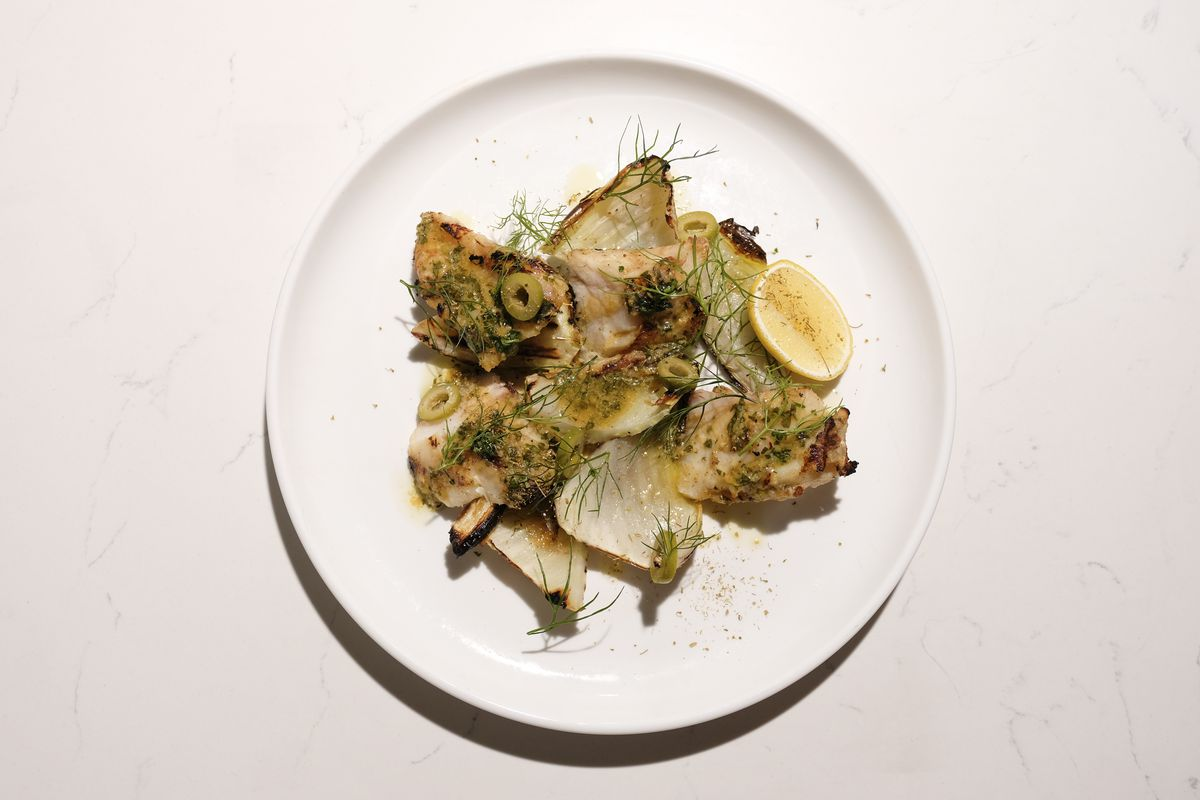 Grilled fish on a white plate with fennel on it