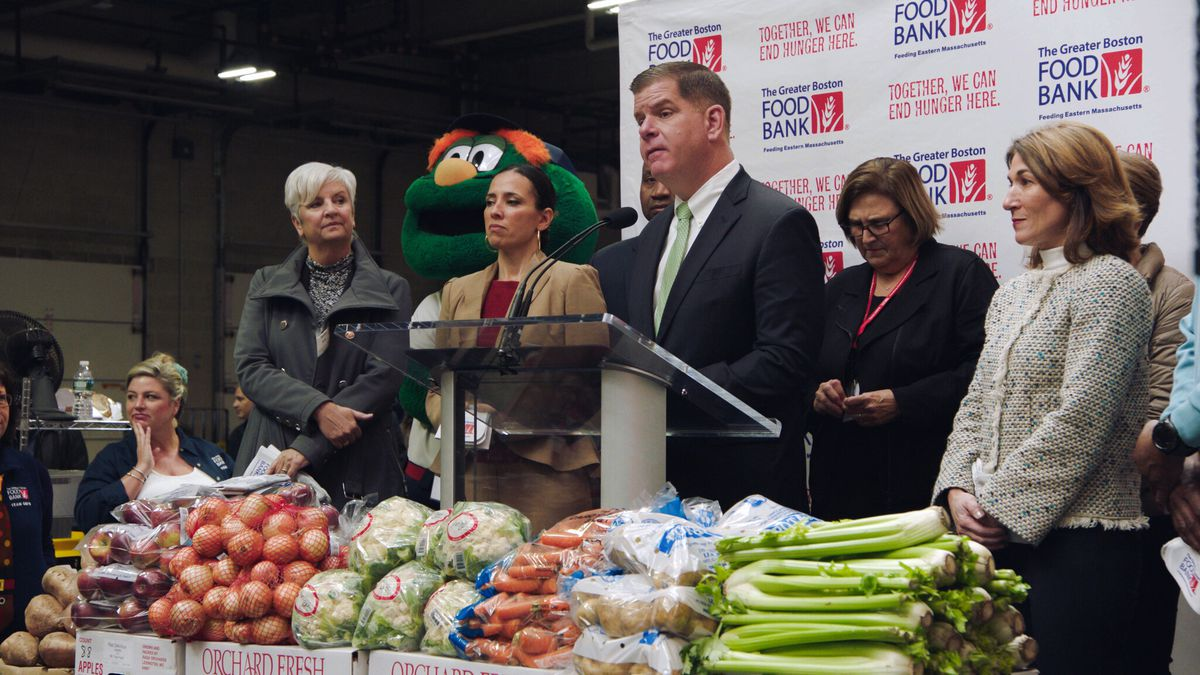 A group of politicians behind a lectern and a wall of produce at a food-bank event in City Hall