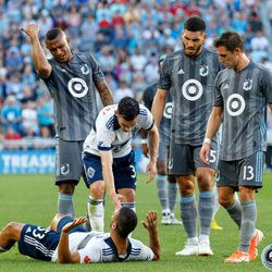 July 27, 2019 - Saint Paul, Minnesota, United States - Vancouver Whitecaps defender Scott Sutter (23) looks for a call as Minnesota United forward Angelo Rodriguez (9) gestures for him to get up during the match at Allianz Field.
