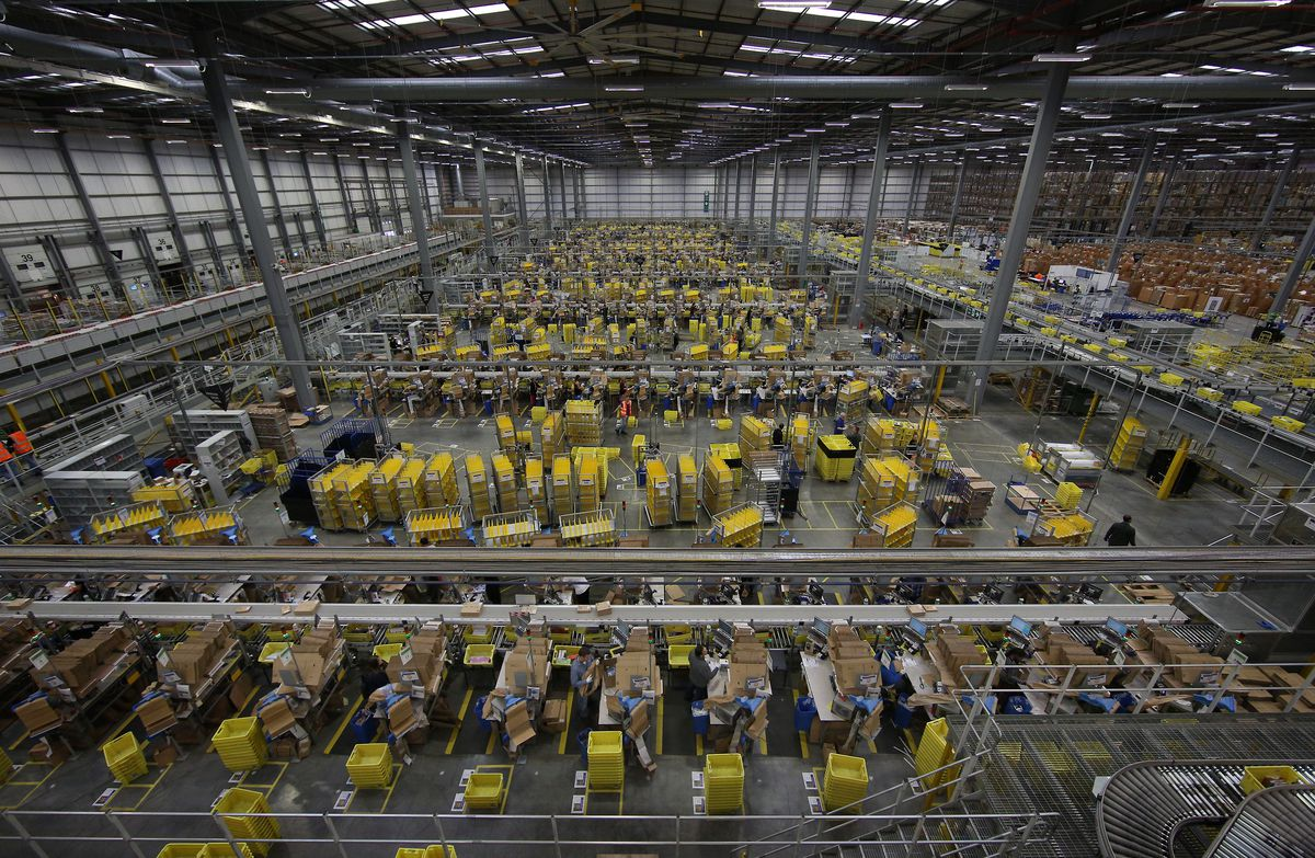 Large aerial picture of giant warehouse full of yellow bins and conveyer belts