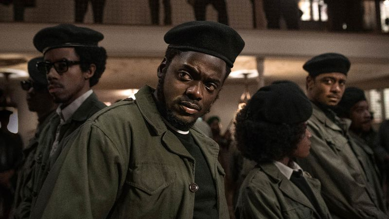 A group of Black Panthers stand looking warily, with Fred Hampton (played by Daniel Kaluuya) at the front of the group.
