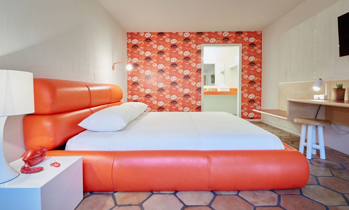 Hotel room with king-sized bed, bright orange puffy headboard and bed frame, bright orange and red wallpaper in lip pattern, a red landline telephone shaped like lips on a white nightstand, and pale clay tile floors.