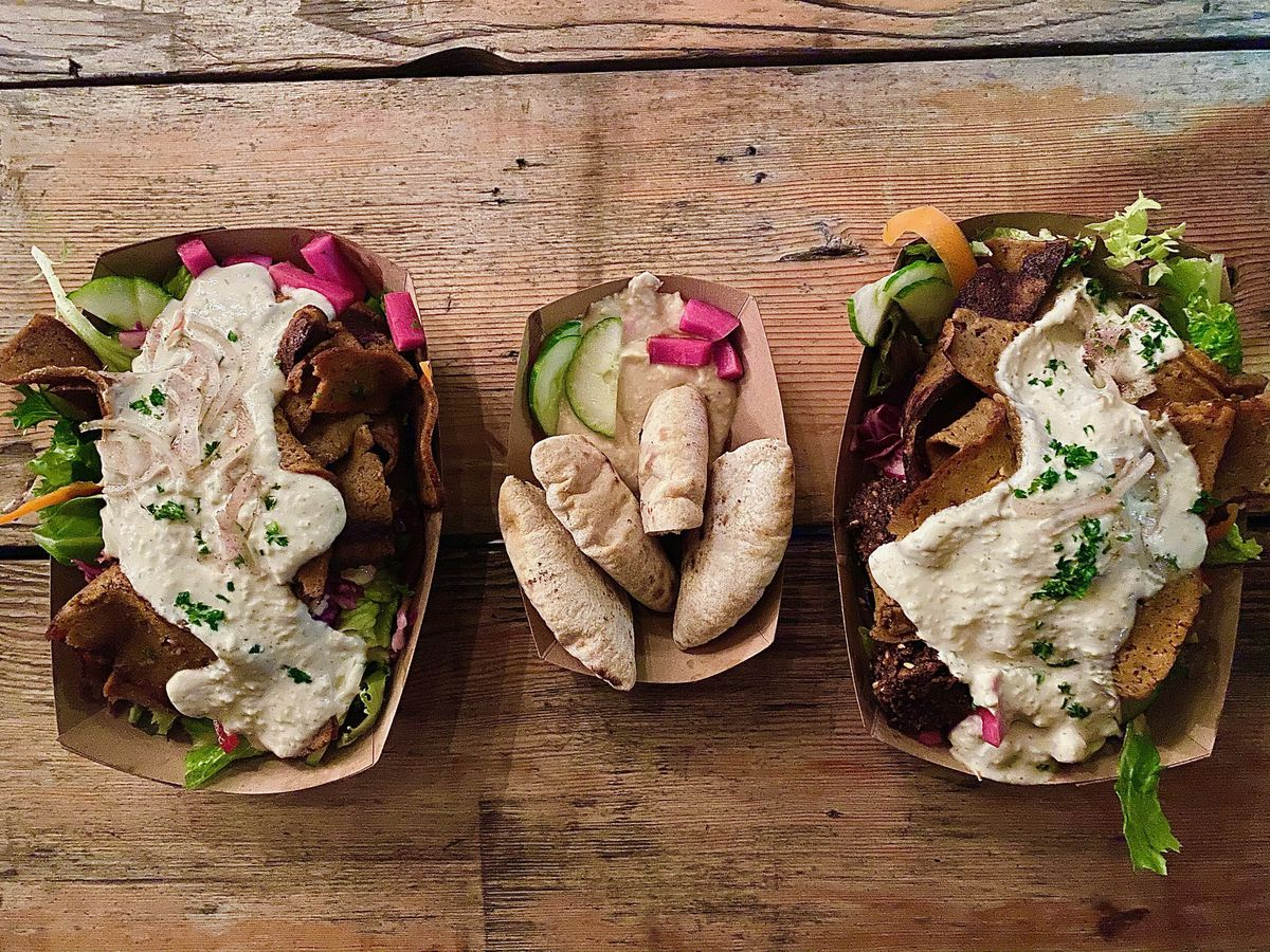 Three boats full of hummus, pita, and vegetables sit on a wood table