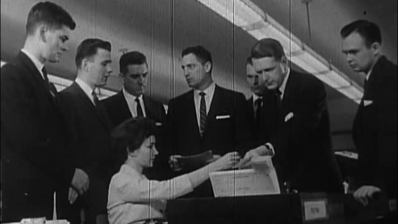A group of white men in suits stands near a woman seated at a typewriter.