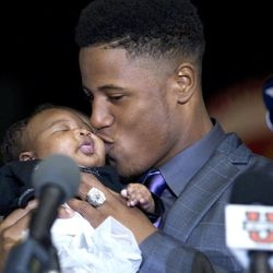 Tracy Howard, the Miramar, Fla. high school football player, kisses his niece, Sanai, before he announced Tuesday, Feb. 1, 2012 that he will attend the University of Miami to play football.