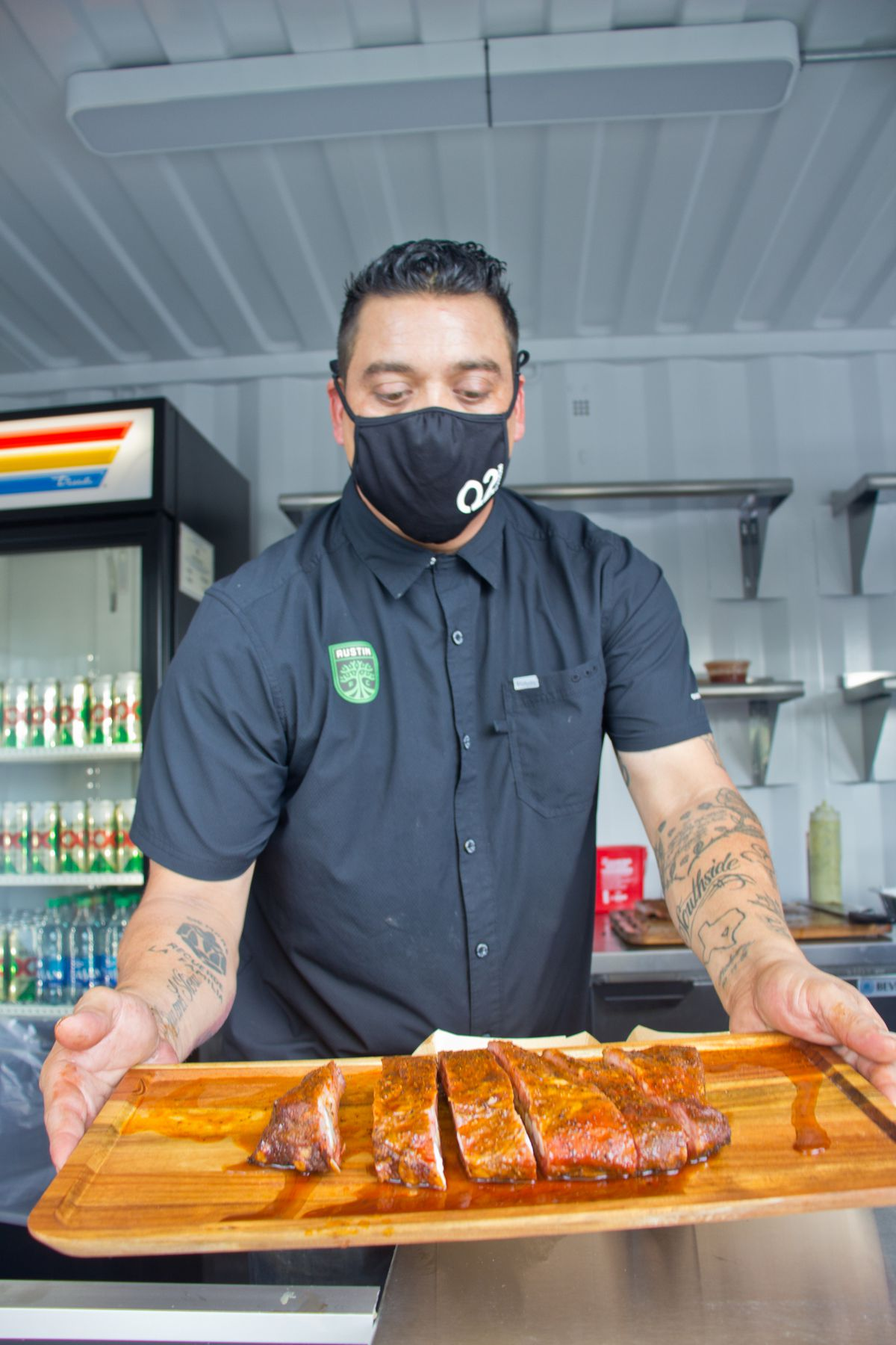 A man in a black shirt and black face mask holding up a wooden board that contains sliced ribs