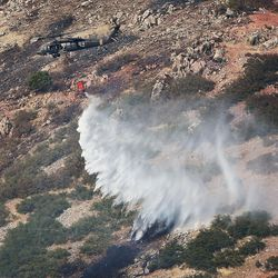 A Blackhawk helicopter drops water on hot spots as a fire burns near Weber Canyon on Tuesday, Sept. 5, 2017.