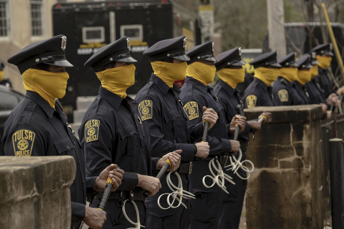 A bunch of policemen, all wearing yellow masks and carrying zip ties, stand in a row.