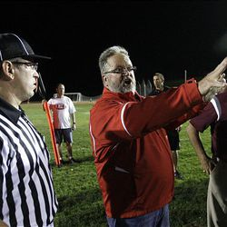 East High principal Paul Sagers confers with referees and coaches as Salt Lake City Fire evacuate fans and players from the  East High School stadium after a fire broke out in a facility building at the field in Salt Lake City  Friday, Aug. 31, 2012. The game will be finished saturday morning.