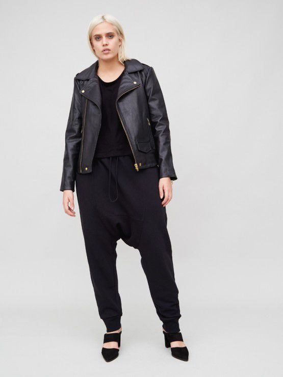 A model in drop crotch black pants and a black leather jacket