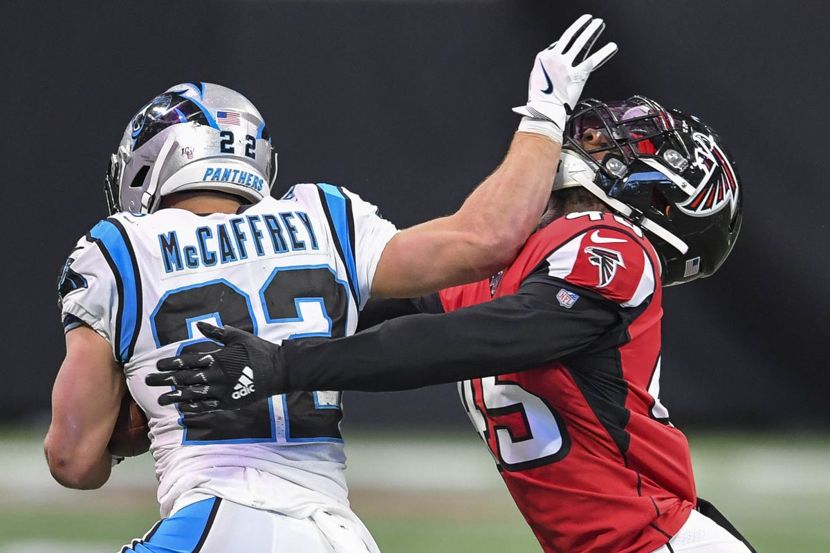 Carolina Panthers running back Christian McCaffrey tries to break out of a tackle by Atlanta Falcons linebacker Deion Jones during the second half at Mercedes-Benz Stadium.