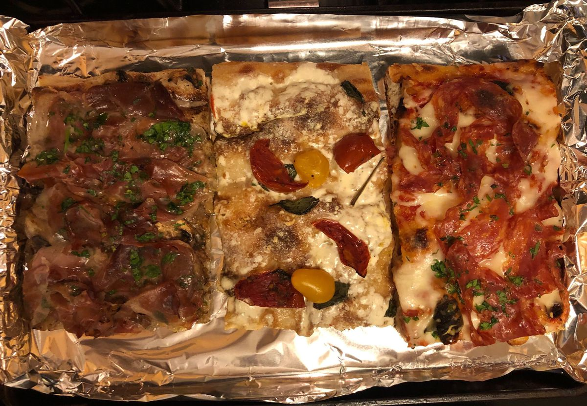 Three square pizza slices laid on a baking sheet covered in aluminum foil