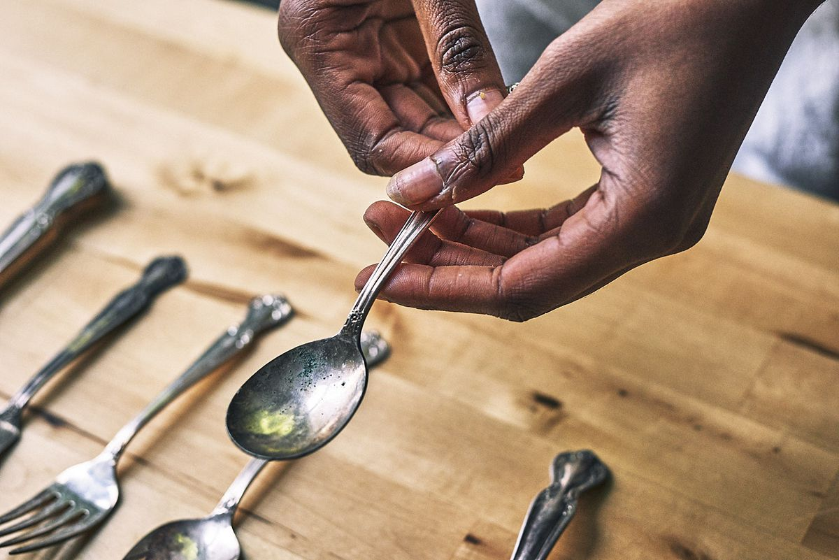 Francesca Chaney picks up a spoon from a set of vintage silverware.