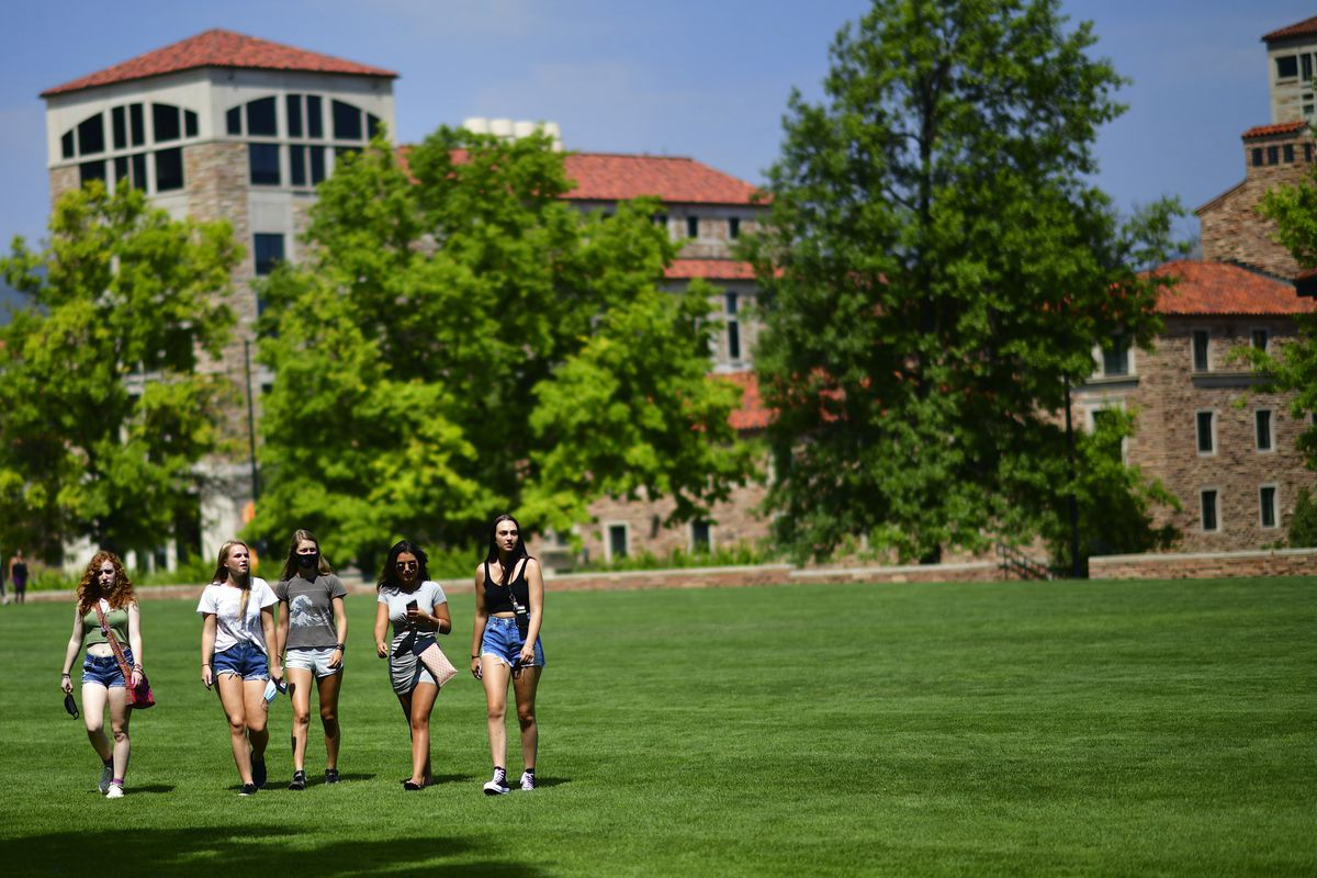 A group of five young women walk across a large field on the campus of Colorado University.