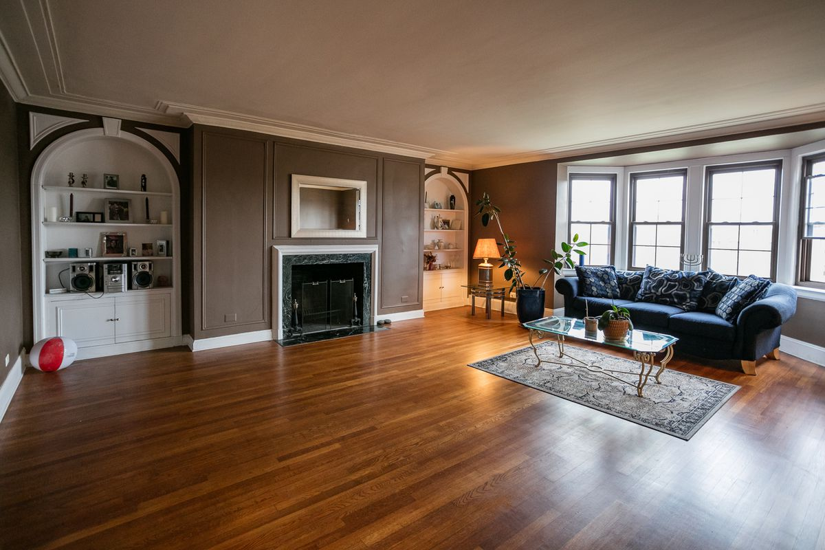 Living room with shimmering hardwood floors and built-in cabinets