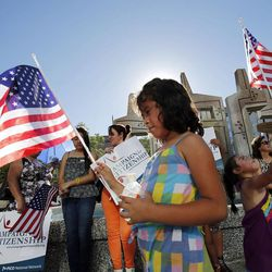 Jessica Vaca, front, and Kaylee Santos hold flags during a prayer vigil in Salt Lake City, Thursday, June 27, 2013.