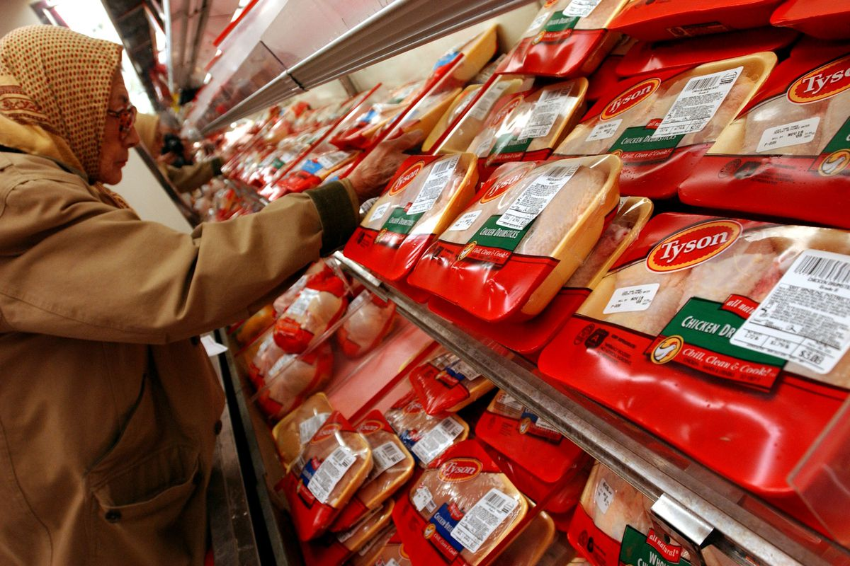 A shopper examines packages of Tyson brand chicken products in the refrigerator section of an Associated Supermarket