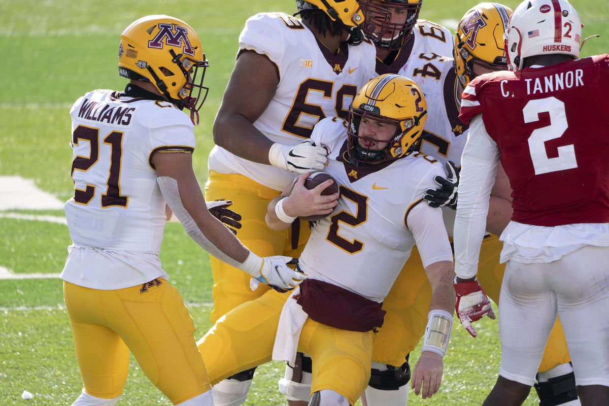 Minnesota Golden Gophers quarterback Tanner Morgan is helped up by teammates after being tackled against the Nebraska Cornhuskers during the second quarter at Memorial Stadium.