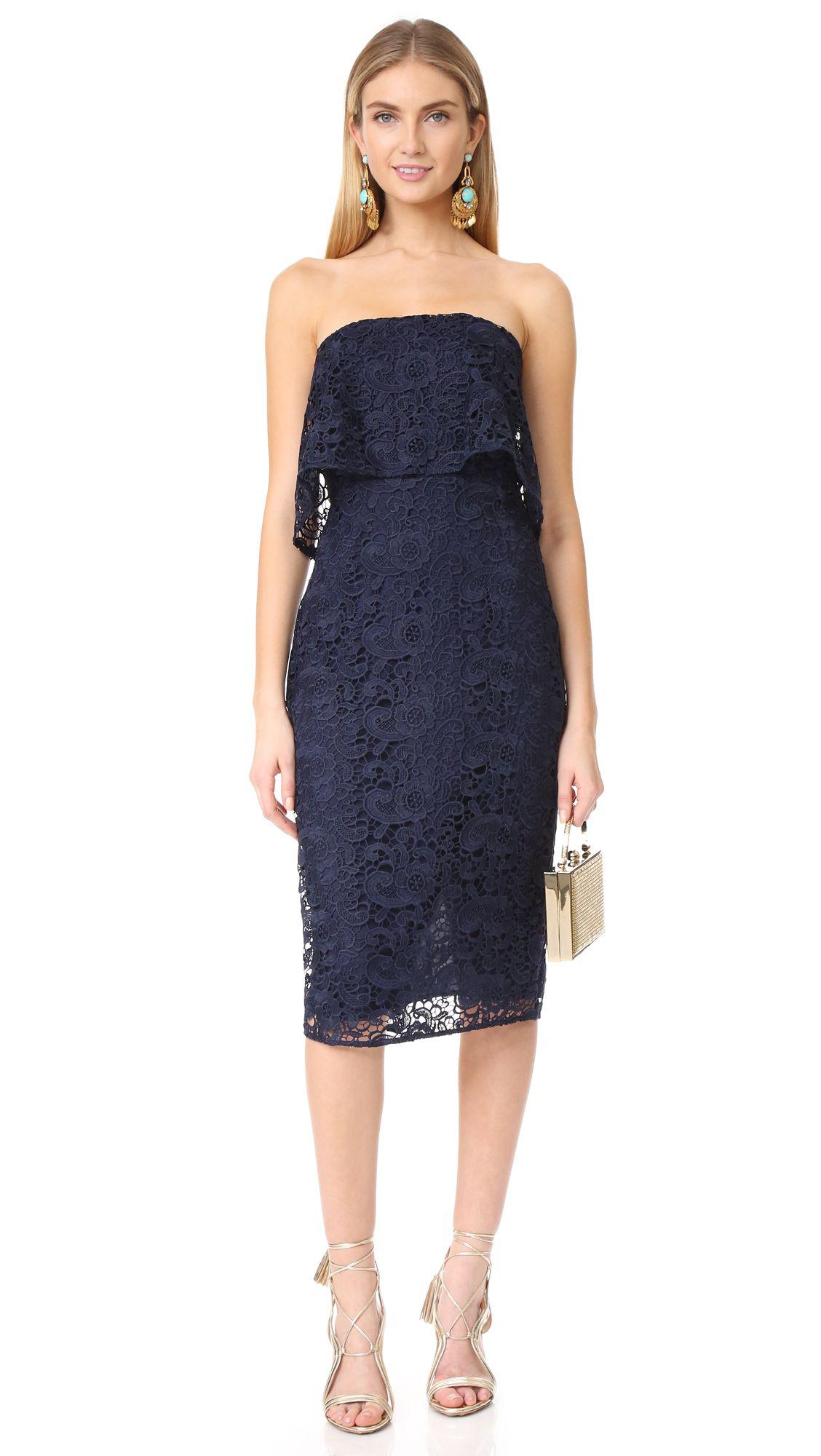 A model wearing a navy blue lace dress