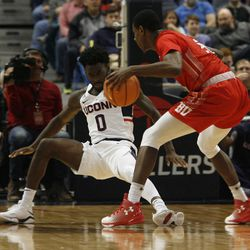 UConn's Antwoine Anderson (0) draws the charge on a Boston University player.