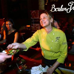 Chef Mary Sue Milliken serves food at the Border Grill restaurant booth at Vegas Uncork'd by Bon Appetit's Grand Tasting event at Caesars Palace. Photo: Ethan Miller/Getty Images