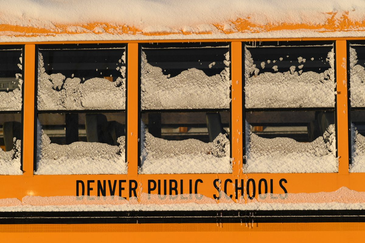Snow and ice cake the windows of a yellow school bus