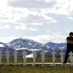 Garrett Bentley looks at crosses Monday for the 13 victims of the massacre at Columbine High School.