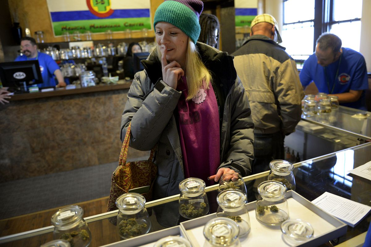 A woman ponders what marijuana she should buy in a Colorado dispensary.