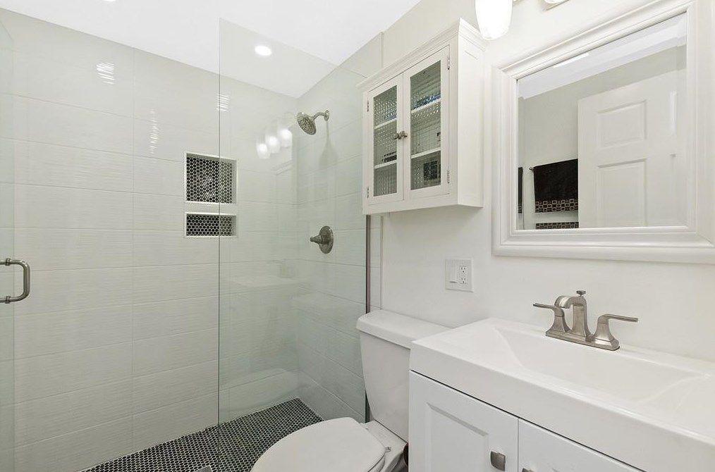 A bathroom with half a glass door along the shower.