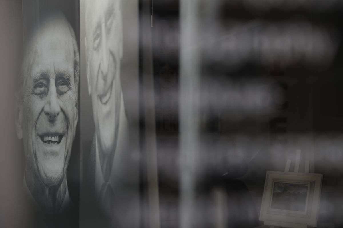 A shop displays a triptych of photos of Prince Philip in Windsor, England, Tuesday, April 13, 2021. Britain's Prince Philip, husband of Queen Elizabeth II, died Friday April 9 aged 99. His funeral service will take place on Saturday at Windsor Castle.