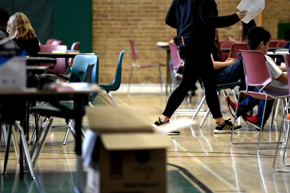 A teacher moves from table to table while teaching one of the two combined sixth grade classes in the gymnasium at Skinner Middle School during the first day of the Denver teacher strike.