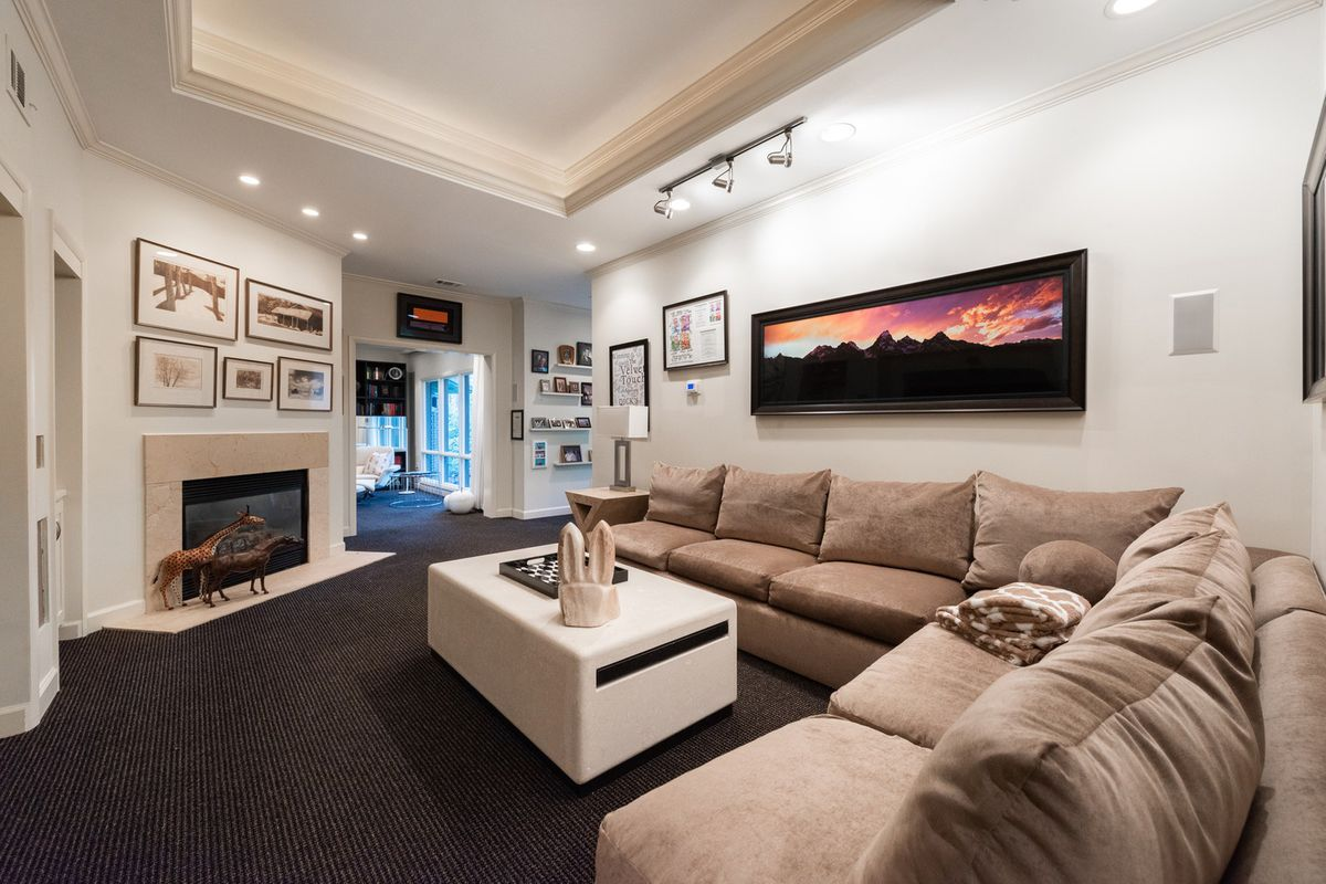 A white room with a fireplace and large beige couch.