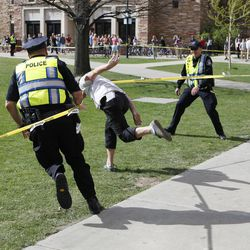 Police try to stop a student as he runs through the police barrier on the Norlin Quad at the University of Colorado in Boulder, Colo., on Friday, April 20, 2012, at 4:20pm. He was run down by police and arrested after crossing the barrier. Police blocked off the quad to prevent a 420 marijuana smoke out.