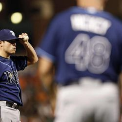 Tampa Bay Rays starting pitcher Matt Moore, left, reacts as pitching coach Jim Hickey walks out to the mound after Moore walked Baltimore Orioles' Robert Andino in the fourth inning of a baseball game in Baltimore, Tuesday, Sept. 11, 2012.