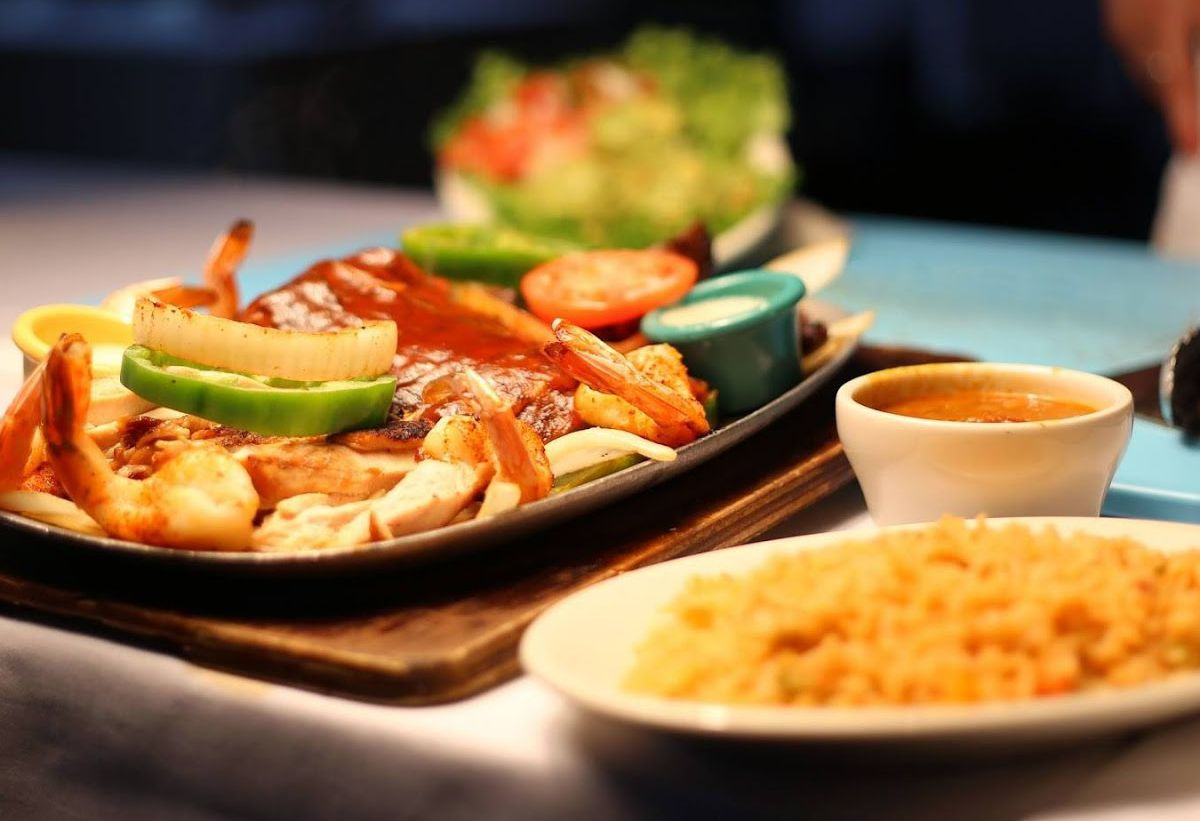 A platter of shrimp fajitas with peppers on a cast iron skillet with a side of Mexican rice