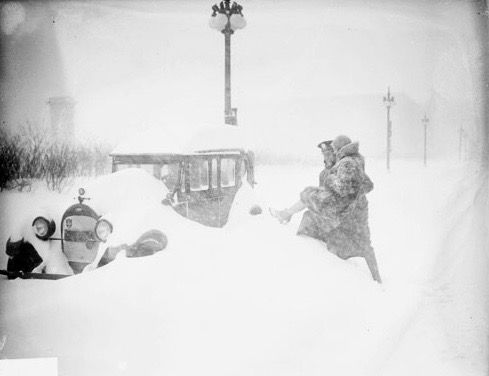 Image of a police officer carrying a woman in a fur coat over a snow drift which has buried an automobile parked on a street inChicago,Illinois. Street lights and snow drifts line the background of the image.