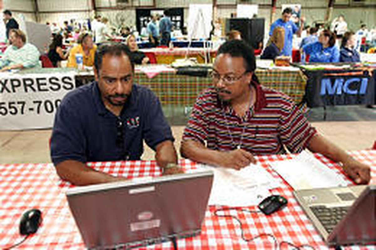 Rick Griffin, left, of Maricopa Work Force Development, helps Hurricane Katrina evacuee Troy Felder, right, of New Orleans, in designing a resume during a job fair at Arizona Veterans Memorial. Felder is attempting to relocate to Arizona. A total of 68,00